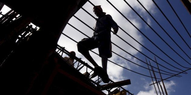 A labourer walks on an iron frame at the construction site of a residential complex on the outskirts...