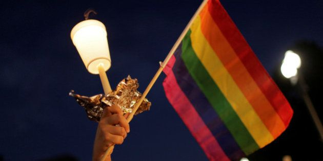 A rainbow flag is held up during a vigil after the worst mass shooting in U.S. history at a gay nightclub...