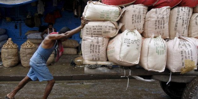 A labourer pushes a handcart loaded with sacks containing tea packets, towards a supply truck at a wholesale...