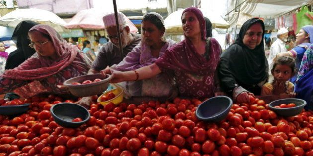 Local residents buy tomatoes from a roadside vegetable market in Ahmedabad, India, August 7, 2015. Entrenched...