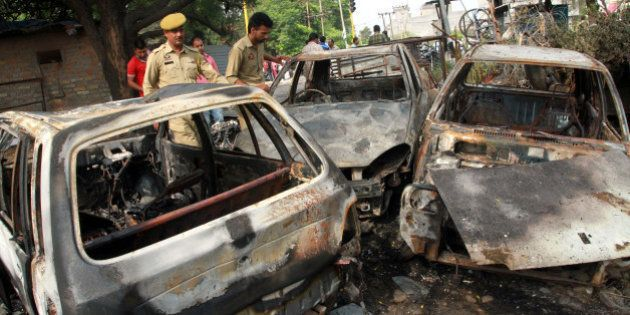 JAMMU, INDIA - JUNE 15: Jammu and Kashmir police men inspect the vehicles burnt by the protesters as...