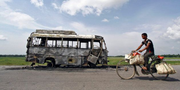 A man rides a bicycle in front of a bus that was burnt by a mob on the national highway near Rongia town...