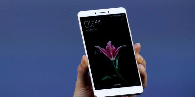 Lei Jun, founder and CEO of China's mobile company Xiaomi, shows its new model Xiaomi Mi Max at its launching...