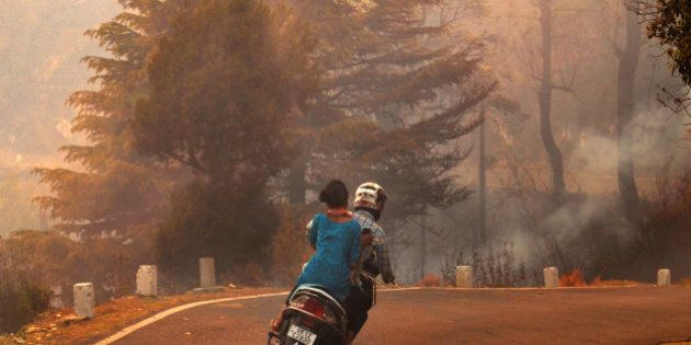 UTTARAKHAND, INDIA - MAY 1: Two wheeler passing through the thick smoke due to the heavy forest fire...