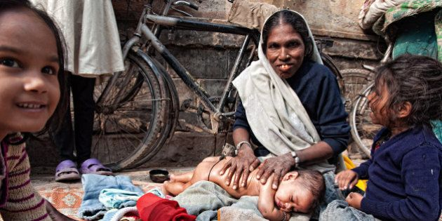 OLD TOWN, VARANASI, UTTAR PRADESH, INDIA - 2011/12/15: Mother giving Shantala massage to her baby and...