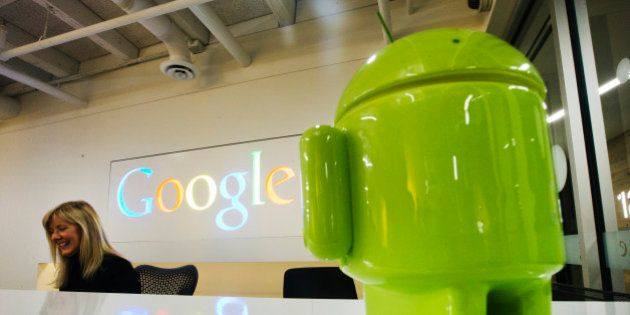 A Google Android figurine sits on the welcome desk as employee Tracy McNeilly smiles at the new Google...