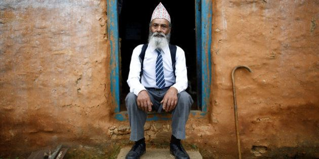 Durga Kami, 68, who is studying tenth grade at Shree Kala Bhairab Higher Secondary School, poses for a picture wearing his school uniform at the door of his one-room house in Syangja, Nepal, June 5, 2016.  REUTERS/Navesh Chitrakar. SEARCH