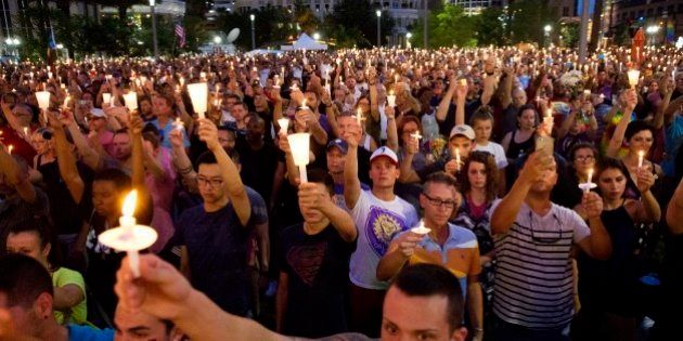 Crowd members hold up candles during a vigil downtown for the victims of a mass shooting at the Pulse...