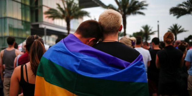 Men, draped in a rainbow flag, embrace ahead of a candle light vigil in memory of victims one day after...