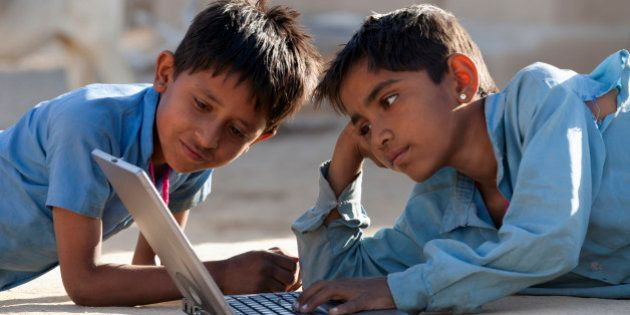 India, Rajasthan, two young boys using laptop