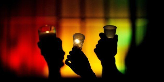 People hold up candles against a rainbow lit backdrop during a vigil for those killed in a mass shooting...