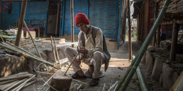 BELDANGI, NEPAL - MARCH 14: Dal Bahadur Bista, 70 years old, cuts bamboos to make furniture in front...