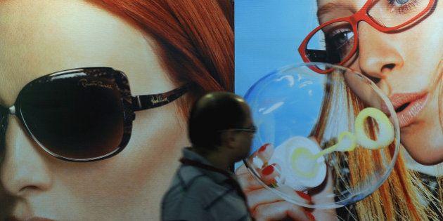 A man walks past billboards advertising luxury designerwear sunglasses in Mumbai on January 30, 2012....