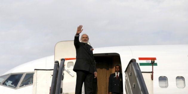 India's Prime Minister Narendra Modi waves as he boards a plane after his trip to Kabul, Afghanistan...
