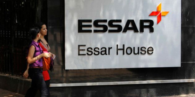 Employees walk past an Essar Group logo outside their headquarters in Mumbai May 20, 2013. India's Economic...