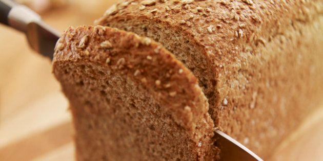 Knife slicing fresh bread