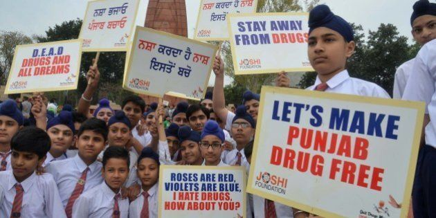 Indian students hold placards as they participate in an anti-drugs awareness march organized by the Joshi...