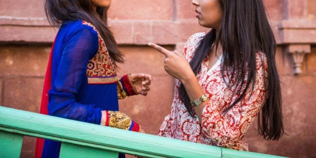 Two young Indian having an argument. One is pointing her index finger at the other to warn