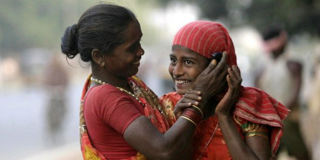 An Indian daily wage laborer holds a mobile phone to another's ear, at a construction site in Bhubaneshwar,...