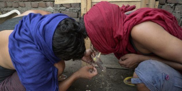 Indian youth inhale drugs on the outskirts of Jalandhar in the north western Punjab province on June...