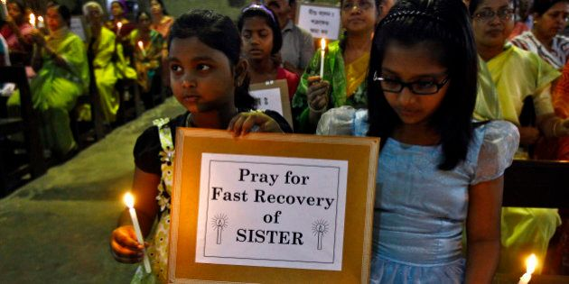 Girls hold a placard and candles during a special prayer service at a church to show solidarity with...