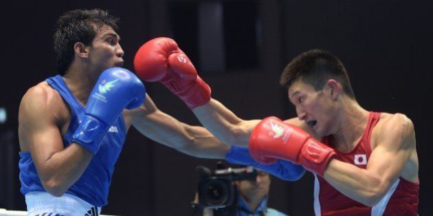 Japan's Masatsugu Kawachi (R) competes against India's Kumar Manoj (L) in the men's bosing light welter...