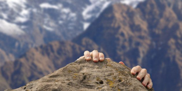 Hands grasp a summit in front of the