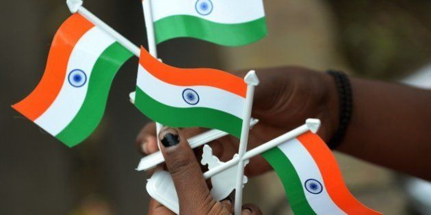An Indian girls selling miniature Indian tricolour flags waits for customers at the corner of a busy...