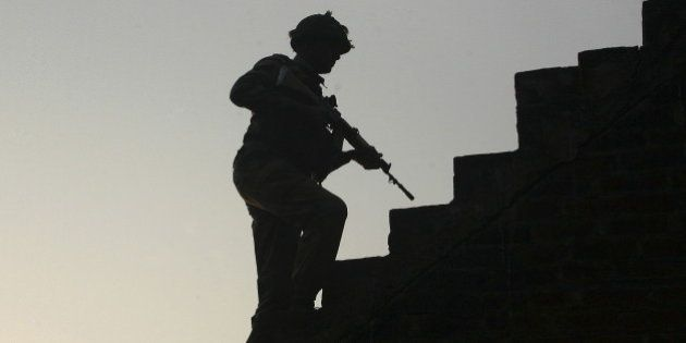 An Indian army soldier climbs up stairs to take his position on the rooftop of a residential house outside...