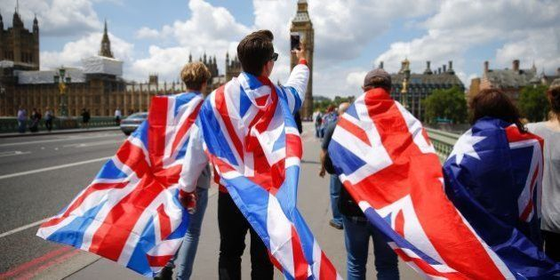People walk over Westminster Bridge wrapped in Union flags, towards the Queen Elizabeth Tower (Big Ben)...