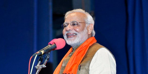 Hindu nationalist Narendra Modi, who will be the next prime minister of India, smiles as he addresses Gujarat state lawmakers and party workers during the appointment of the state's new chief minister in Gandhinagar May 21, 2014. Modi on Wednesday resigned as the state's chief minister and invited the leaders of Pakistan and other neighbours to his inauguration next week in an unprecedented move, signalling his aspirations to be a regional leader. REUTERS/Amit Dave (INDIA - Tags: POLITICS ELECTIONS)