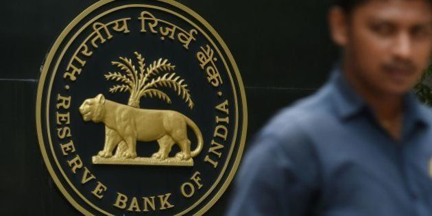 A pedestrian walks past India's central bank - Reserve Bank of India (RBI) logo in Mumbai on June 7,...