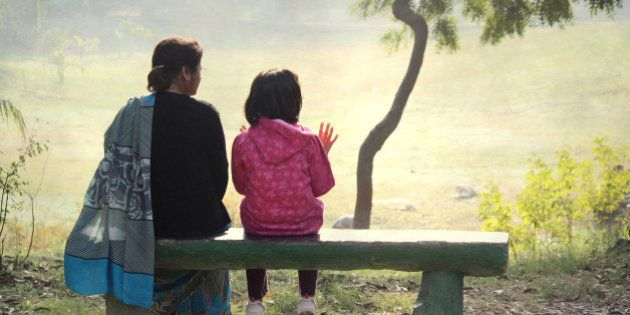 A child sitting with her grandmother on a bench in the