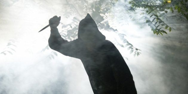 hooded monster with knife in forest coming towards camera light and fog