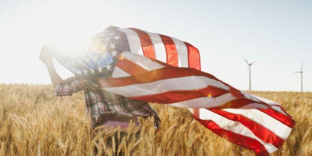 USA, Oregon, Wasco, Girl (12-13) flying american flag in wheat