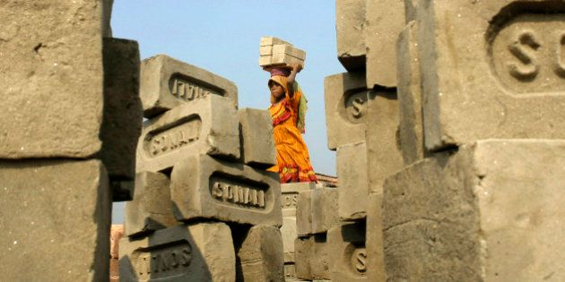 A child labourer carries bricks inside a brick factory on the outskirts of the eastern Indian city of...