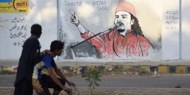 Pakistani cyclists ride past a wall image of late Sufi musician Amjad Sabri alongside a street in Karachi...