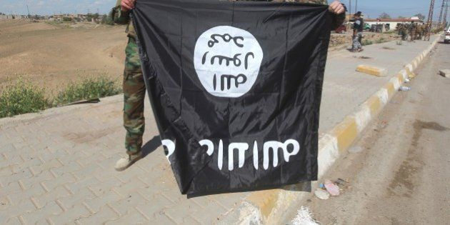 Iraqi Sunni and Shiite fighters pose for a photo with an Islamic State (IS) group flag in the Al-Alam...
