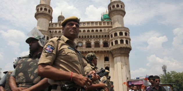 Indian policemen stand guard in front of the landmark Charminar during Friday prayers at Mecca Masjid...