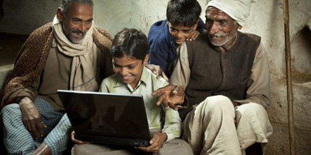 Happy village boy sitting cross-legged and using a laptop in the company of his father, grandfather and...