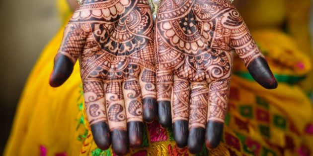 An Indain bride's hand with henna tattoos. An Indian bride showing her palms painted with a traditional...