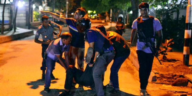 People help an unidentified injured person after a group of gunmen attacked a restaurant popular with...