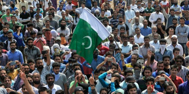 SRINAGAR, INDIA - JUNE 15: People shout anti-national slogans and raise flag of Pakistan during funeral...