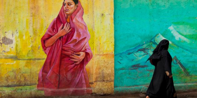 Local muslim woman dressed in a in black burqa is walking pass a wall painting in the city of Bangalore,...