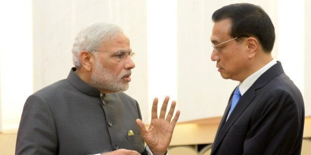 Indian Prime Minister Narendra Modi (L) talks with Chinese Premier Li Keqiang after a news conference...