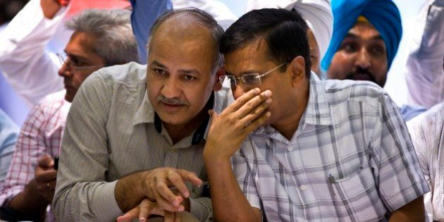 Delhi Chief Minister Arvind Kejriwal, right, speaks to his deputy Manish Sisodia at a farmer's rally...