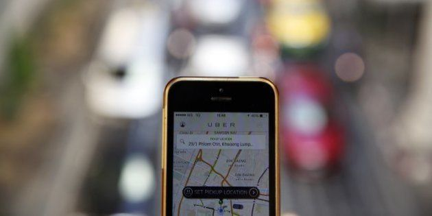 A phone running the Uber application is held above the traffic in central Bangkok December 10, 2014....