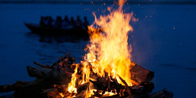 A tourist boat goes past the burning flames of a pyre at a cremation ground on the banks of river Ganges...