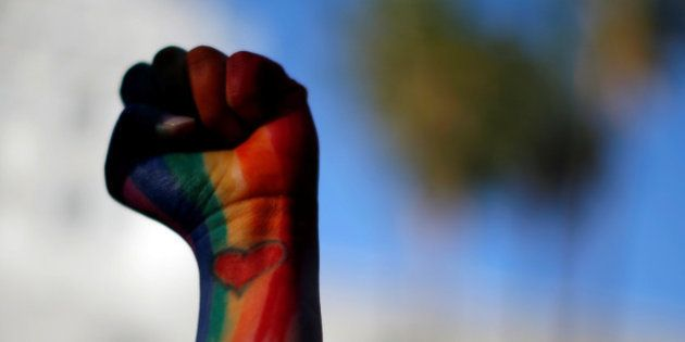 Dominique Hernandez holds up her fist painted in the colors of a rainbow, with a heart on her pulse,...