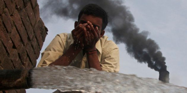 A labourer drinks water as smokes rise from a chimney of a brick factory at Togga village on the outskirts...